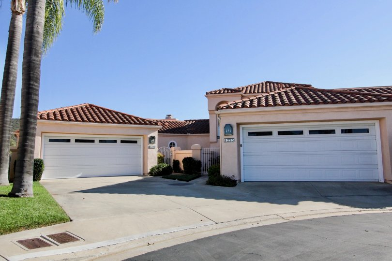 Two white garage doors on pink units near palms inside The Colony at San Marcos CA