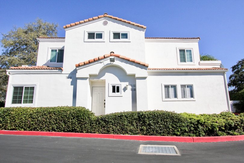 Two story white building with a white door near hedge inside Villa Aspara At San Marcos CA