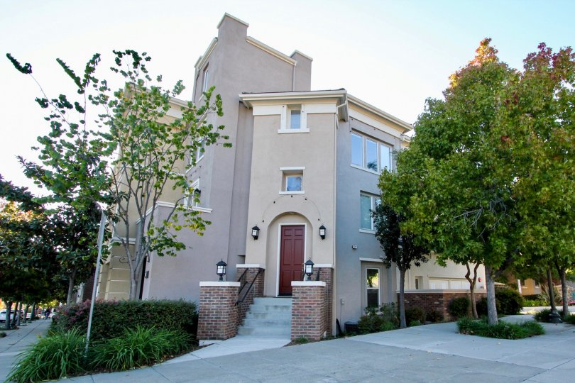 Four story residence with two large brick pillars & trees in Village Square in San Marcos CA