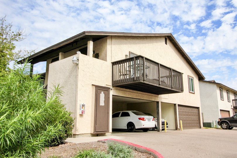 Carefree East, Santee, CA.  A large brown houe with a 3 car garage, full deck, columns, and green landscaping.