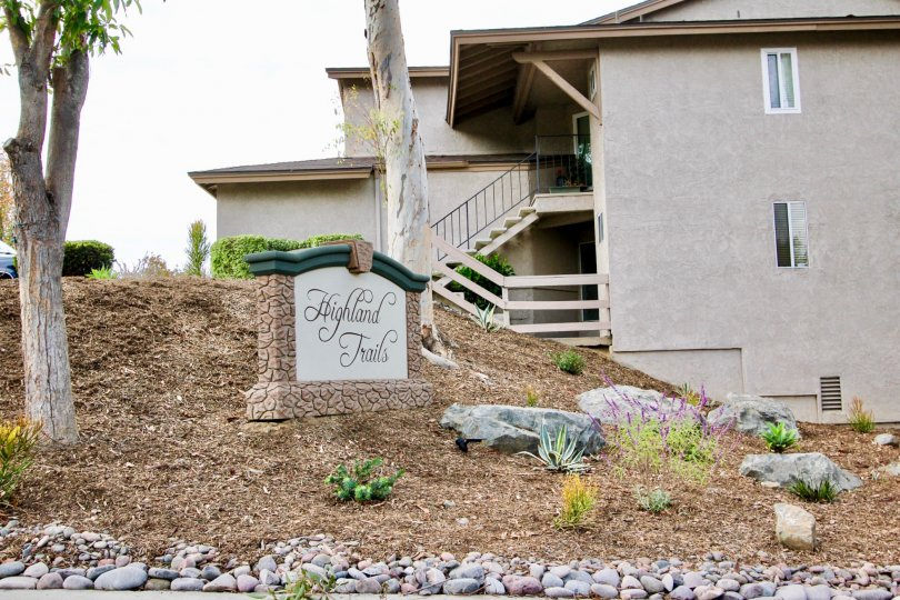 White & black sign on a hillside inside Highland Trails at Santee CA