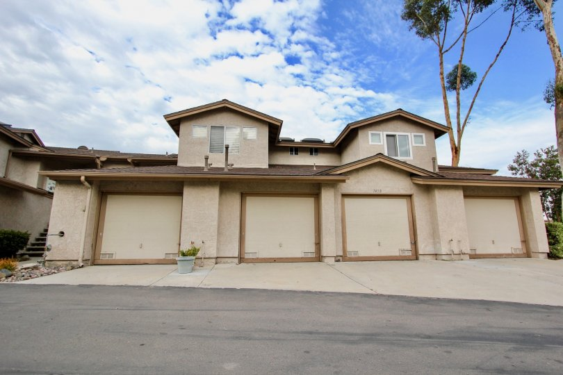 Tan two story house with four garages and cement driveway, house number 7458 in Highland Trails, Santee, CA