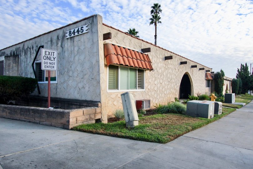 Building 8445, a stucco and tile building showing the exit driveway in community Horizon Village, Santee, CA