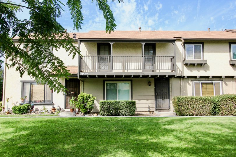 Two story apartments behind a green yard in the Magnolia Meadows in Santee California