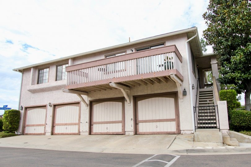 A view of four garage doors and a balcony on the second floor in the Mission Martinique neighborhood in Santee, California