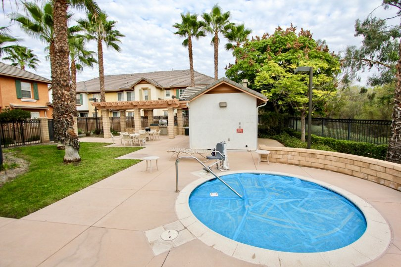 A blue tarp covers the in ground hot tub in the community area at the Palmilla Apartments in Santee California