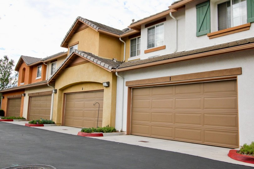 Four closed brown garage doors on the first floor of orange, white, and yellow townhomes in the Palmilla community in Santee California