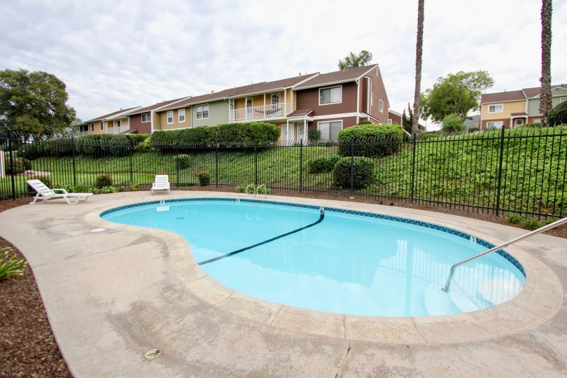 A pool with a concrete patio and lawn chairs for sitting in Pepperhill Townhomes