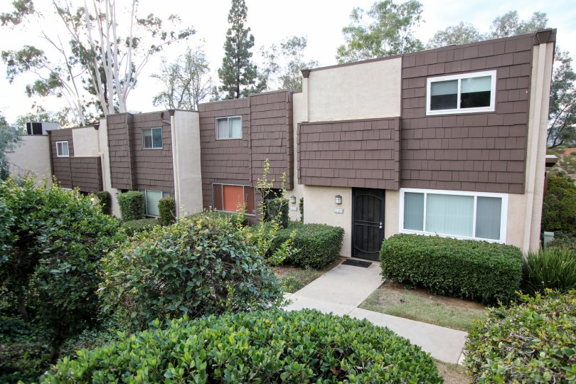 Rio Terrace,: Santee  , California,trimmed bushes,brown and white building
