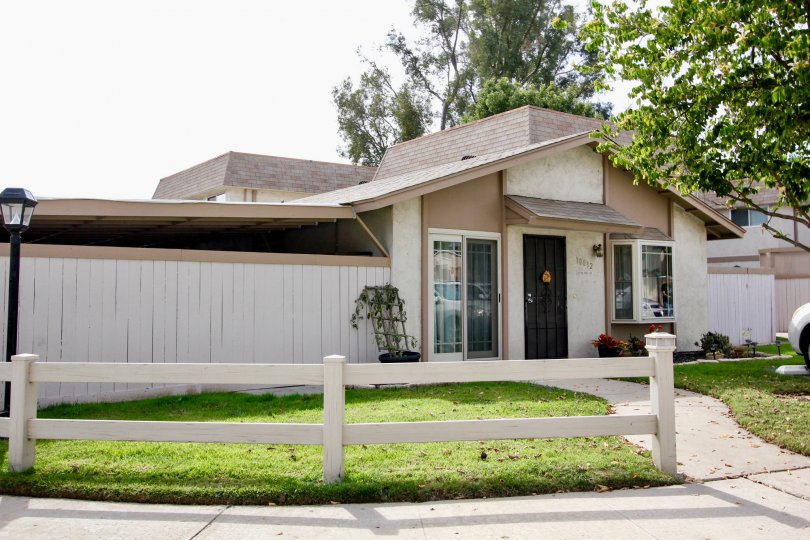 A sunny day in the area of Santana Ranch, wooden fence, condo, gated door, car, walkway