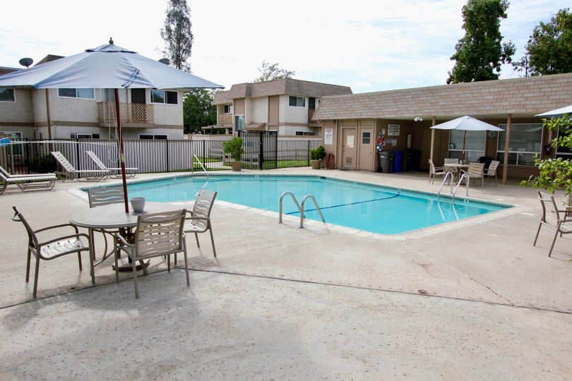 A shared pool area for an apartment complex in Santee, California featuring a clubhouse and concrete patio