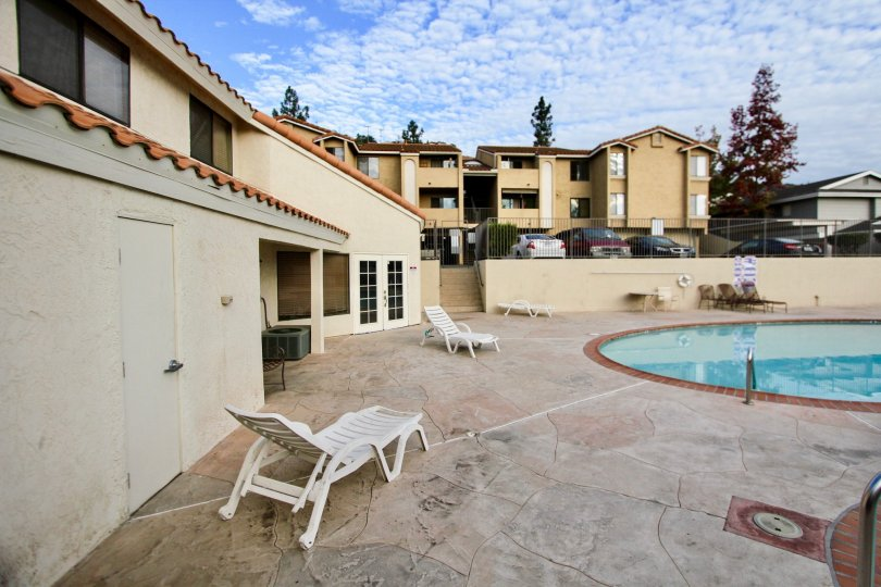 A pool deck in Towne Villas with lawn chairs and parking area
