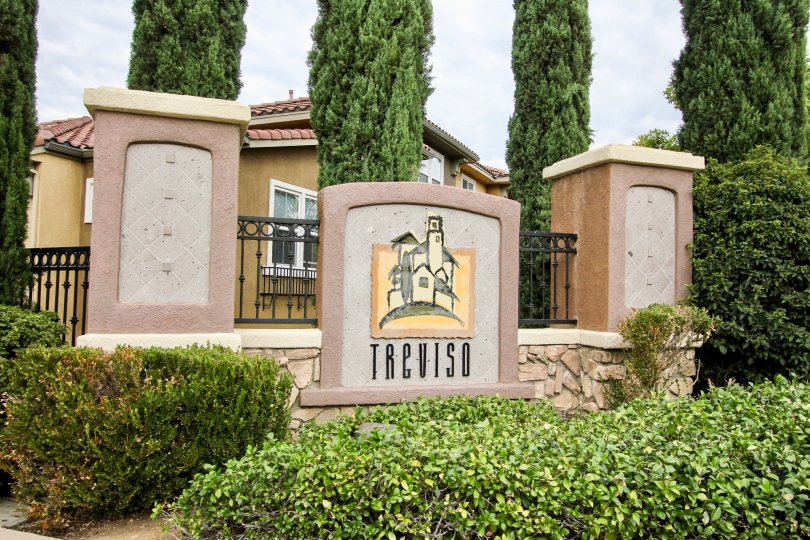 Beautiful rod iron and stone entrance with lush vegetation to the Treviso Community in Santee California.