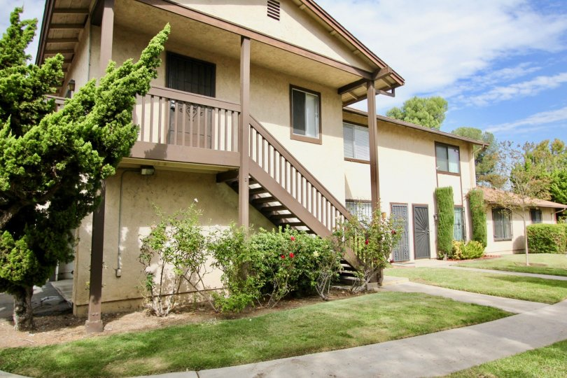 A sunny day in the area of Carefree South, outside, condos, stairs, trees, windows, flowers