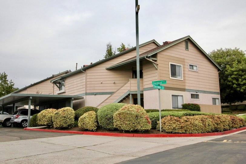 Ranchwood Park apartments with covers for the cars and some colorful bushes