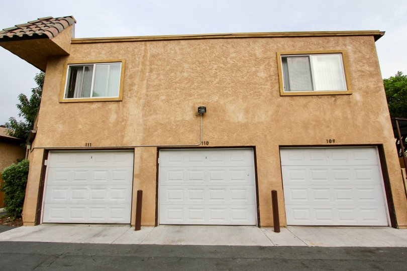 The exterior of a three-car garage in Spring Valley, California in the community of San Remos Villas. The exterior of the garage is brown with two windows and the garage numbers are 111, 110, and 109.