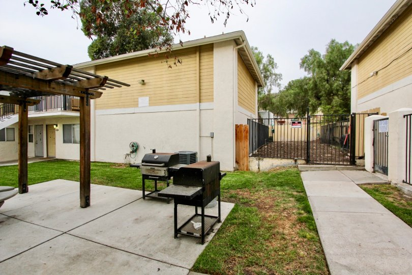 Concrete patio and walkways in a private fenced in area with barbeques and pergola in Spring Valley