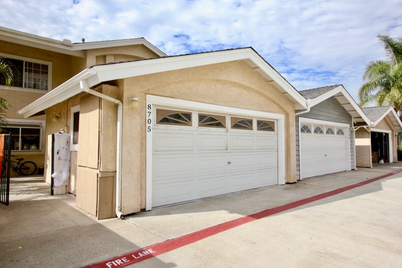 Double car garage parking units on a back lane with concrete paved backyards in Sunset Ridge