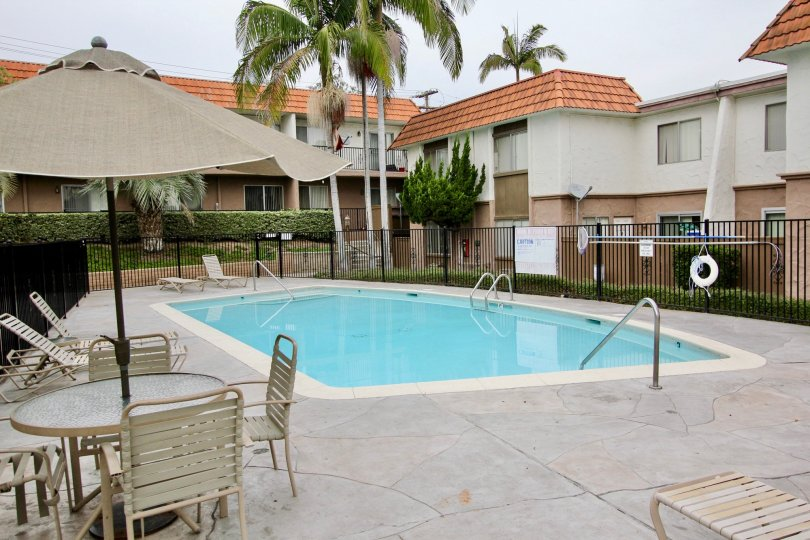 THE BUNGALOW IN THE TERRAZA WITH THE SWIMMING POOL, TABLES, UMBRELLA, PLANTS, TREES