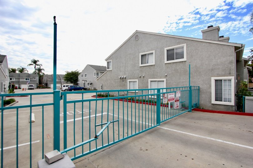 A teal colored metal gate secures the parking lot to the Valencia Canyon condos