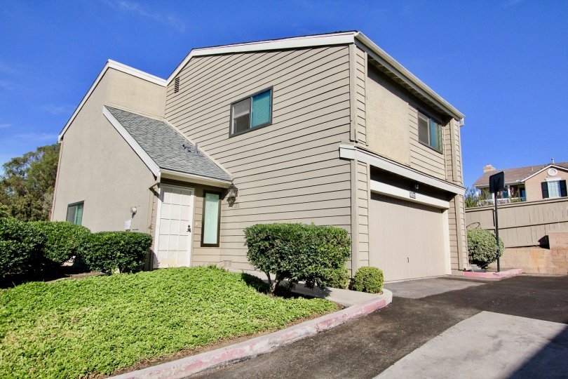 A two storey gray house with some bushes during a sunny day in Durian Place Townhomes, Vista, CA