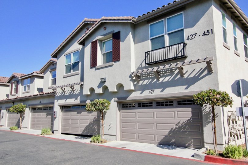 A series of gray townhouses with spanish tile roofs in the Santa Fe Walk community of Vista, CA