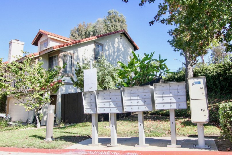 A row of mailboxes with some trees and houses behind it during a sunny day in Vista Knolls, Vista, CA