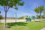 A sandy play area for the kids at Box Springs with a swing set and slides