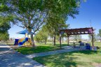 A covered playground and picnic bench at the park in Moreno Valley Ranch