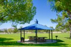 A solid roof gazebo shades two picnic tables at the Mountain View Park