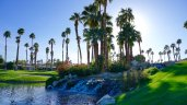 The sun sets behind palm trees around the lake at Palm Desert Resort Country Club