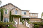Concrete steps and white column banister lead to the ivy covered front of this Bella Lago come