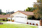 Single Story home with two car garage and large shade providing tree