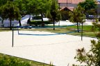 Residents enjoy playing in white sand volley ball court walking distance from community center.