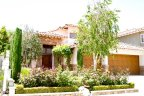 Beautiful two story home with lush green lawn and rose plants resides in peaceful Cantamar neighborhood