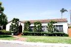 Plumosa Park home with juniper trees shaped in between each window in San Diego