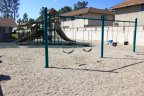 A sandy playground with swings and jungle gym at Village Townhomes